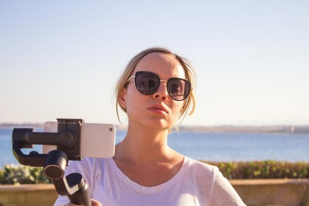 Mulher, filmando, pôr do sol, ligado, viagem, vídeo, blogger, fazer, vídeo, com, gimbal, e, telefone móvel
