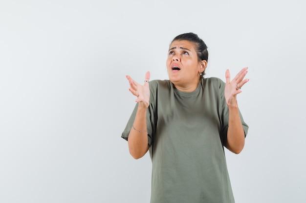 Mulher fingindo manter algo na camiseta e parecendo alarmada