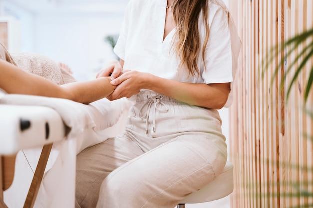 Mulher fisioterapeuta dando uma massagem a um cliente na clínica