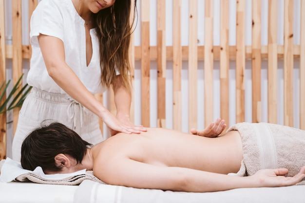 Mulher fisioterapeuta dando uma massagem nas costas para um cliente na clínica