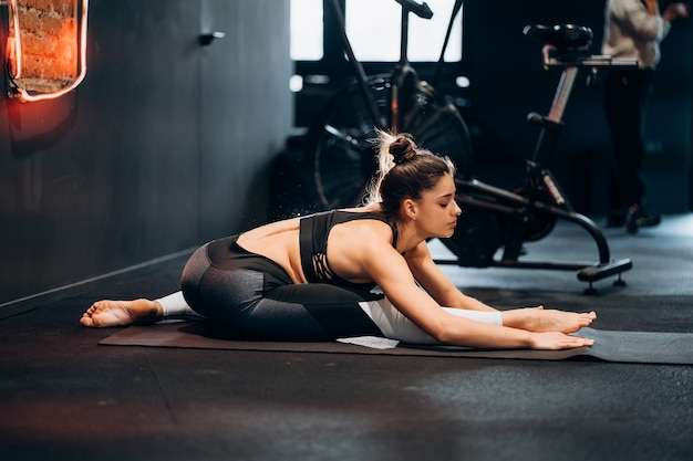 Mulher fitness alongando-se fazendo exercícios de pilates