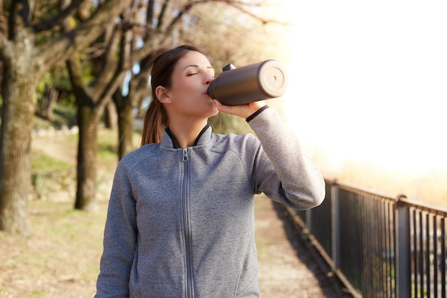 Mulher fitness bebendo água de uma garrafa após o treino
