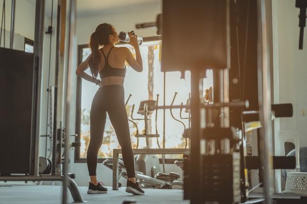 Mulher fitness bebendo água em pé e descansando na academia.