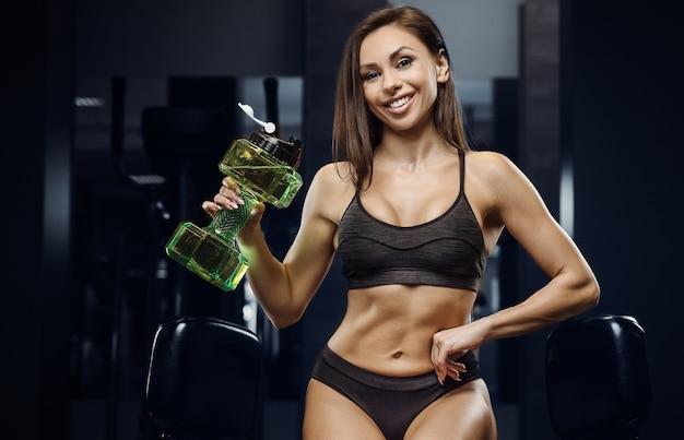 Mulher fitness bebendo água fazendo exercícios na academia
