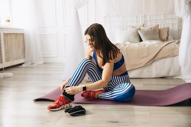 Mulher fitness colocando pesos de tornozelo para o esporte ajustando os punhos de peso do tornozelo antes de começar o treino no conceito de saúde e fitness