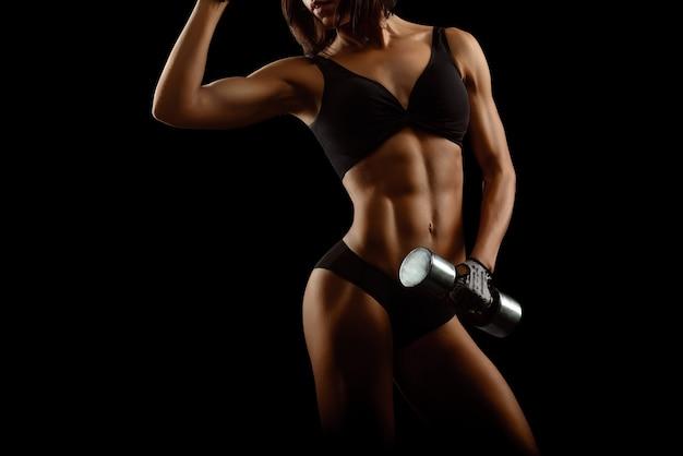 Mulher fitness com corpo perfeito segurando halteres