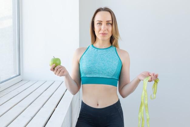 Mulher fitness com fita métrica e maçã sorrindo feliz olhando para frente