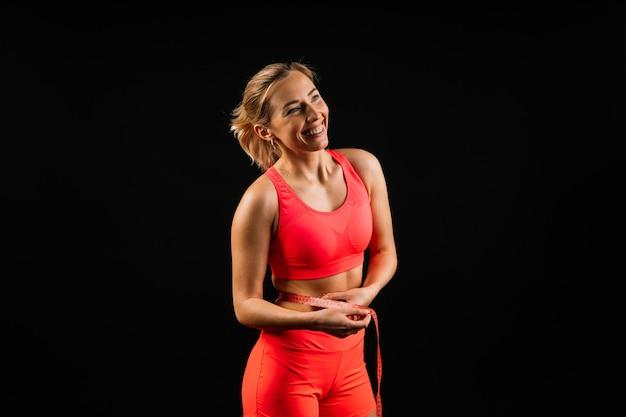 Mulher fitness com fita métrica mostrando a cintura no fundo do estúdio