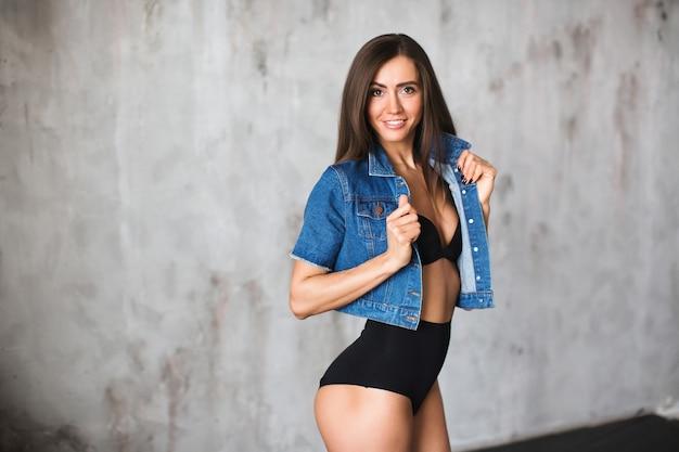 Mulher fitness com halteres fazendo um exercício em um fundo escuro
