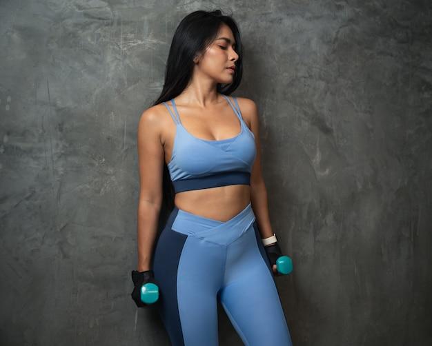 Mulher fitness com halteres na parede escura