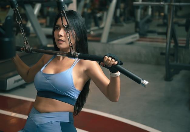 Mulher fitness com máquina de treino no ginásio