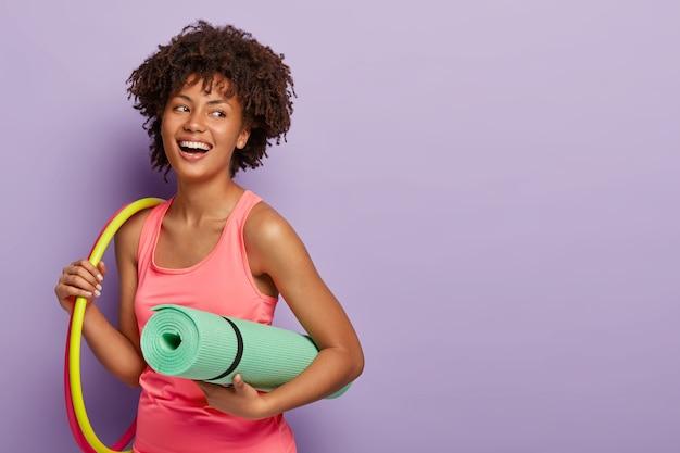Mulher fitness com pele escura, trabalha com bambolê, segura um karemat enrolado para treinar