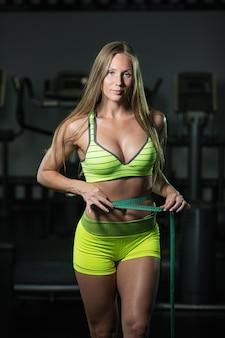 Mulher fitness com roleta mede a circunferência do abdômen