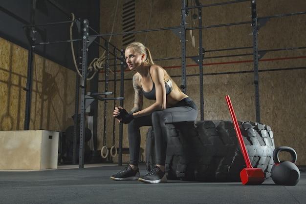 Mulher fitness descansando após treino de marreta na academia. garota loira apta fazendo uma pausa após o treino