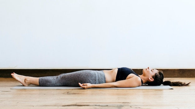 Mulher fitness em pose shavasana