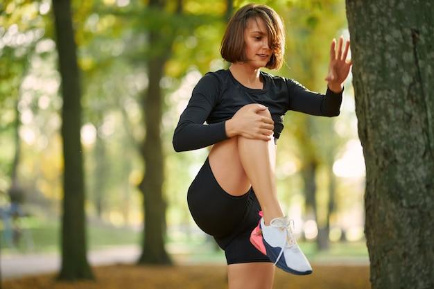 Mulher fitness em roupa ativa esticando as pernas ao ar livre