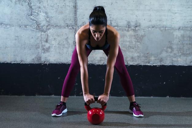 Mulher fitness em roupas esportivas se exercitando com peso de sino de chaleira na academia