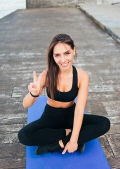 Mulher fitness em roupas esportivas sentada no tapete de ioga e mostrando o símbolo v na praia