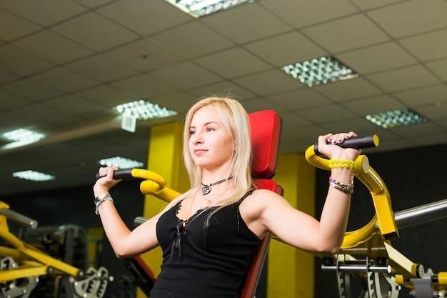 Mulher fitness executa exercícios com aparelho de ginástica na academia