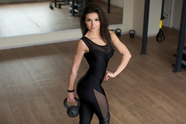 Mulher fitness exercitando crossfit segurando bíceps de treinamento de força com kettlebell