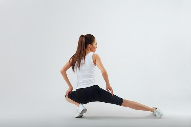 Mulher fitness fazendo exercícios de alongamento