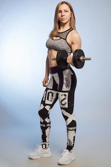 Mulher fitness fazendo exercícios de crossfit segurando halteres
