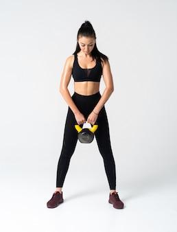 Mulher fitness fazendo exercícios de crossfit segurando o sino da chaleira