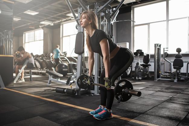 Mulher fitness fazendo exercícios de levantamento terra no estúdio de esportes