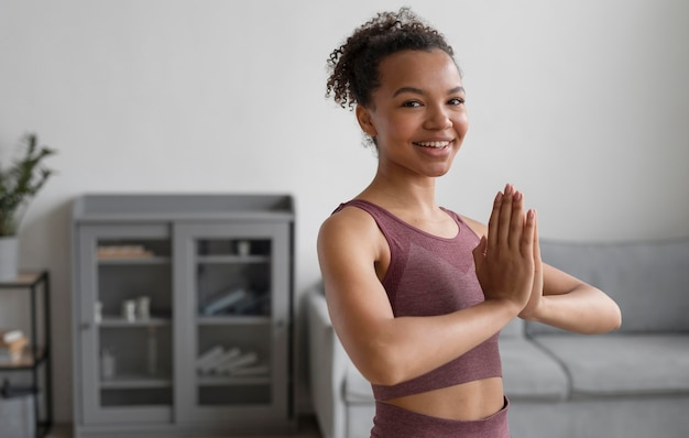 Mulher fitness fazendo ioga em casa