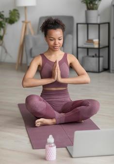 Mulher fitness fazendo ioga em uma esteira de ioga em casa