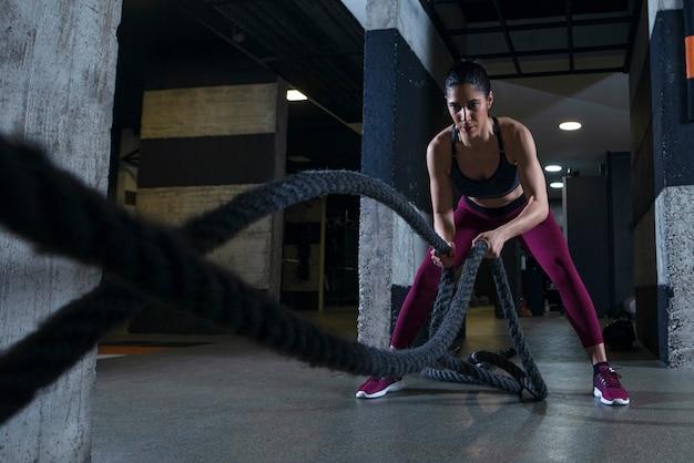 Mulher fitness malhando com cordas de batalha na academia