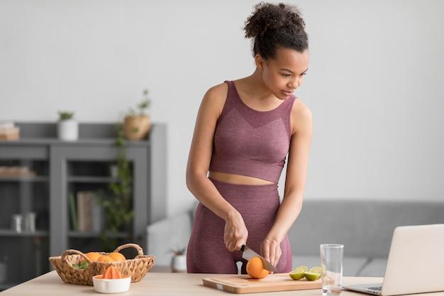 Mulher fitness preparando um suco de fruta saudável