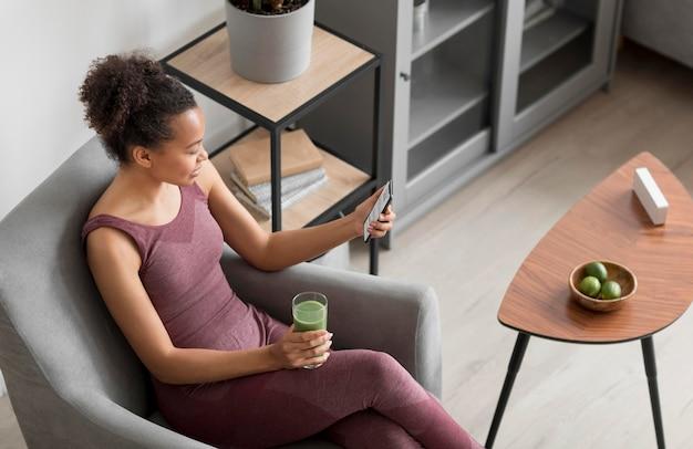 Mulher fitness tomando um suco desintoxicante enquanto usa um smartphone
