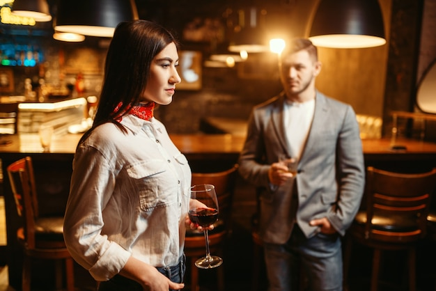 Mulher flertando com homem, casal em bar.