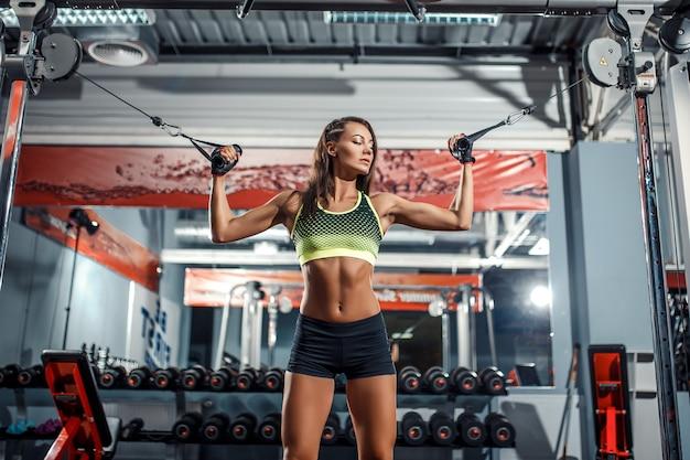 Mulher flexionando os músculos na máquina de cabo no ginásio