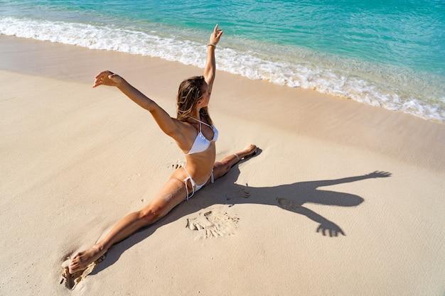 Mulher flexível em biquíni branco fazendo ioga na praia e aproveitando o banho de sol, a areia branca e a água do mar azul claro