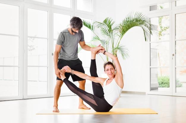 Mulher flexível fazendo uma pose de ioga de alongamento com a ajuda de um personal trainer em uma academia de ginástica com janelas e copyspace