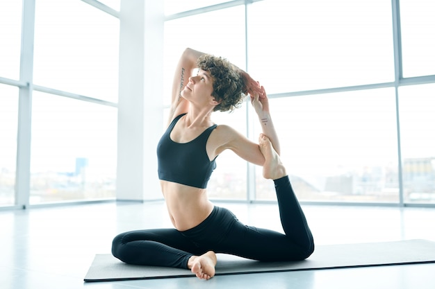 Mulher flexível no colchonete fazendo ioga ao lado de uma grande janela