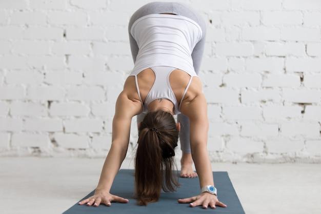 Mulher flexível que estica as costas e os braços