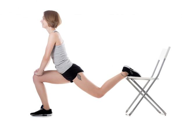 Mulher flexível que estica com uma cadeira