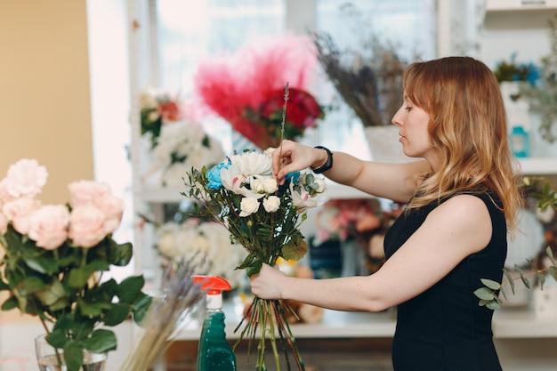 Mulher florista faz buquê em boutique de flores