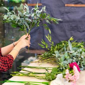 Mulher florista fazendo buquê de flores na loja