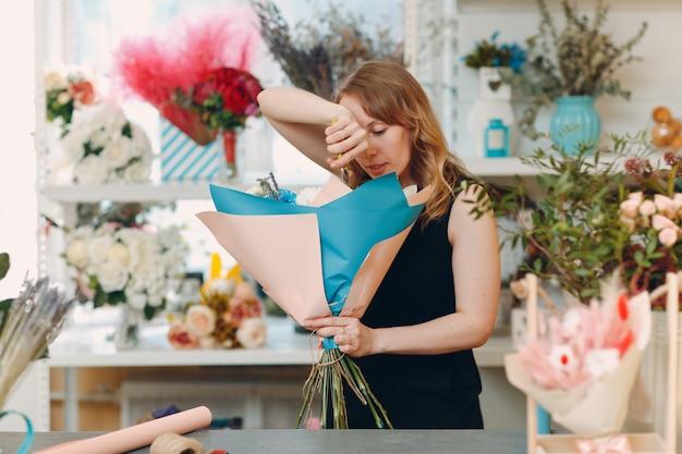 Mulher florista fazendo buquê em boutique de flores