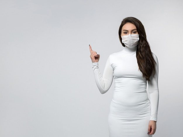 Mulher focada aviso sobre covid em vestido branco e máscara protetora branca