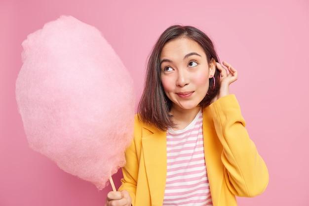 Mulher focada com uma expressão pensativa segurando um delicioso algodão doce no palito e usando roupas da moda