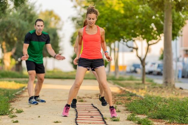Mulher focada fazendo circuito de fitness no parque e malhando com seu personal trainer.