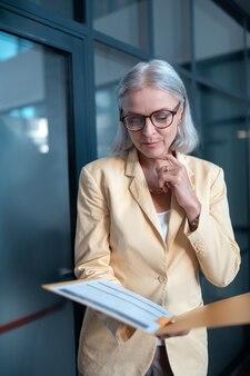Mulher focada. foto vertical de uma mulher de negócios de cabelos grisalhos elegante e concentrada em uma jaqueta amarelo-claro olhando para os documentos na pasta
