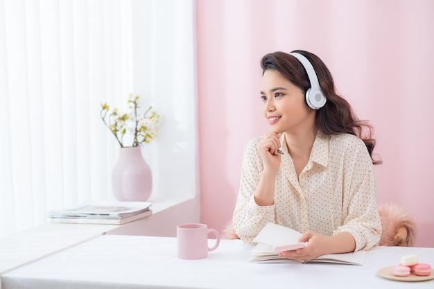 Mulher focada usando fones de ouvido escrever caderno