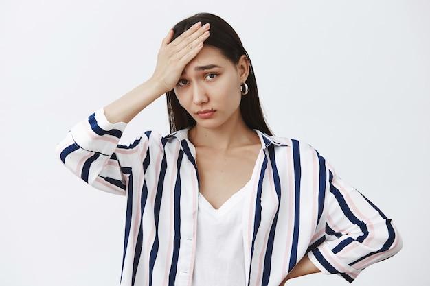 Mulher fofa cansada e sombria em uma blusa listrada, segurando a palma da mão na testa, sentindo-se sob pressão, exausta e olhando chateada para a parede cinza