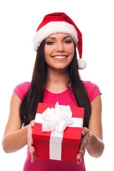 Mulher fofa com chapéu de papai noel dando um presente de natal